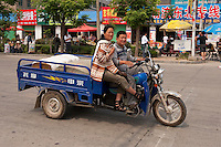 Daytime landscape view of a man and a woman riding a motorized tricycle on a road in Bozhou in Qiáochéng Qū in Anhui Province.  © LAN