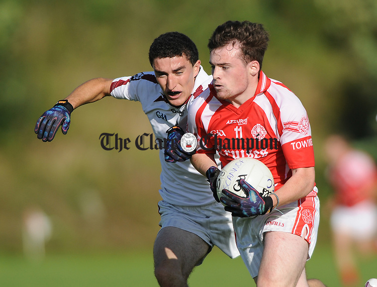 Kieran Roche of Liscannor in action against Eibhin Courtney of Eire Og during their senior championship game in Corofin. Photograph by John Kelly.