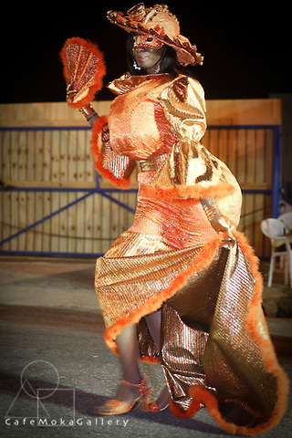 Trinidad Carnival, traditional mas, a man dressed as a Dame Lorraine in orange dress, hat and fan