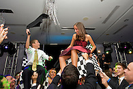 Brother and sister being lifted in chairs during <br />