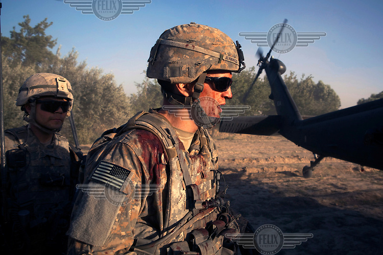 US Army soldier Staff Sgt. Andrew Jennings Company C, 2nd Battalion, 508th Parachute Infantry Regiment, wounded by shrapnel in a firefight, boards a waiting medevac helicopter from Charlie Company, Sixth Battalion, 101st Aviation Regiment in the middle of a firefight near Kandahar.