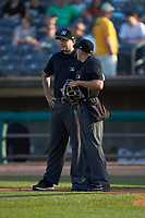 Base umpire Ben Fernandez (left) chats with home plate umpire Kelvis Velez between innings of the South Atlantic League game between the Lexington Legends and the West Virginia Power at Appalachian Power Park on June 7, 2018 in Charleston, West Virginia. The Power defeated the Legends 5-1. (Brian Westerholt/Four Seam Images)