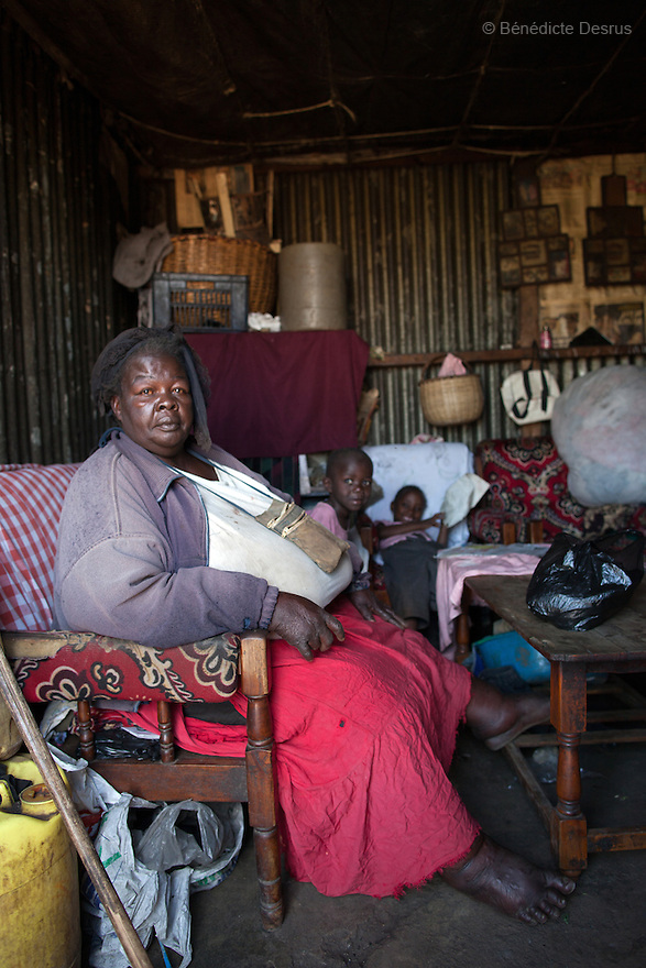 """Susan Kalai aka """"Mama Safi"""", a 53 year old Kenyan woman with severe morbid obesity, sits with her family at her home inKawangware slum in Nairobi, Kenya on December 8, 2012. """"Mama Safi""""lives on less than $1 USD a day, selling vegetables and fried potatoes in the street in front of her house. She has 7 children, the youngest one is 9 yearsold. She suffersfrom several obesity-related diseases. She can't walk, has a lot of pain in her legs and back and also has difficulties to breathe. She says """"I was born big. I was always like this.Both my parents and my sister are big too. So for me it's normal. Nothing is wrong with me"""".She has no knowledgeabout obesity and she can't go to the doctor to get treated because she has no money to pay for it. She is afraid to die of a heart attack. Although large parts of Africa areplaguedwith malnutrition, the continent must now also deal with another problem:obesity.Obesity is fast becoming a serious problem in Kenya and even the poorest are now being affected. Obesity rates are climbing around the world and they are rising faster in developing countries than in developed ones. (Photo by Benedicte Desrus)"""