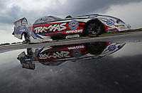 Sept. 1, 2012; Claremont, IN, USA: The car of NHRA funny car driver Courtney Force reflects in a rain puddle as her car is towed back to the pits during qualifying for the US Nationals at Lucas Oil Raceway. Mandatory Credit: Mark J. Rebilas-