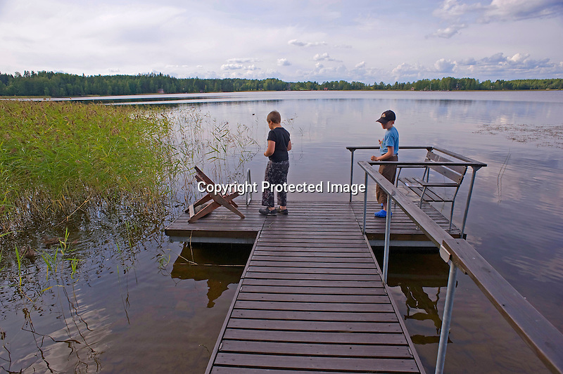 Young Boys on Dock Feeding Ducks at Summer Cottage in Finland
