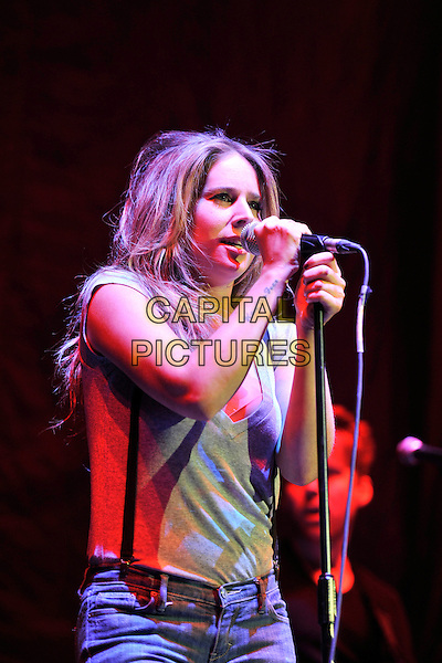LUCIE SILVAS .Performing live at the O2 Arena, London, England, UK, April 15th 2011..music concert gig on stage half length microphone singing  jeans braces  grey gray t-shirt hand tattoo writing side .CAP/MAR.© Martin Harris/Capital Pictures.