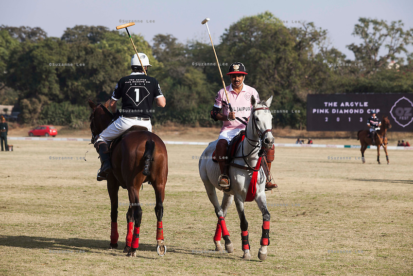 Greg Johnson (left), captain of the Australian team and Maharaj Narendra Singh (right) captain of the Jaipur team pass each other during a game between the Royal Jaipur Polo Team (in pink) and the Western Australia Polo Team (in black) for the Argyle Pink Diamond Cup, organised as part of the 2013 Oz Fest in the Rajasthan Polo Club grounds in Jaipur, Rajasthan, India on 10th January 2013. Photo by Suzanne Lee