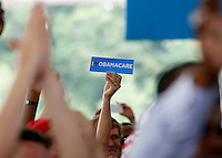 A supporter holds up an Obamacare sticker during rally for President Barack Obama in Charlottesville, VA.