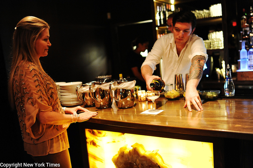 Ivy, a new concept restaurant, makes its debut to a invited guests in New Orleans, Nov. 11, 2013. Bartender Jeff Bucker pours champagne for owner Rebecca Singley just before opening its door for the first time.