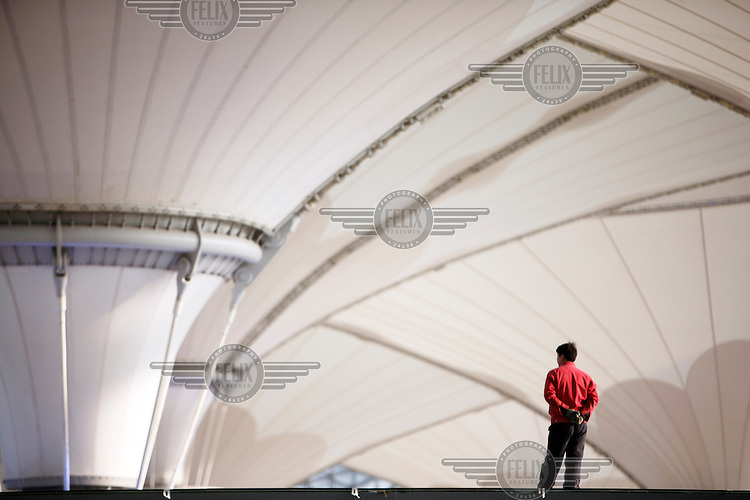 A worker standing on top of a platform overlooking funnel-like structures erected at the 2010 World Expo site.