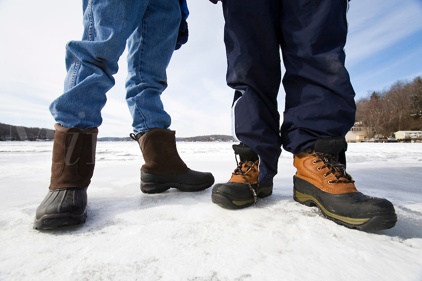 Two boys wearing boots and standing on a frozen lake.