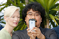 "Tilda Swinton and Bong Joon-ho at the ""Okja"" photocall during the 70th Cannes Film Festival at the Palais des Festivals on May 19, 2017 in Cannes, France. Credit: John Rasimus /MediaPunch ***FOR USA ONLY***"