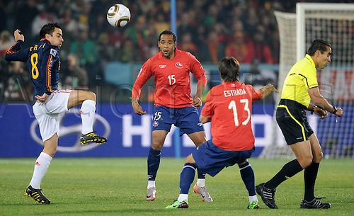 Spain's Xavi Hernandez (L) and Chile's Jean Beausejour (15) and Marco Estrada challenge for the ball as Mexican referee Marco Rodriguez turns away during the 2010 FIFA World Cup group H match between Chile and Spain at Loftus Versfeld Stadium in Pretoria, South Africa 25 June 2010.