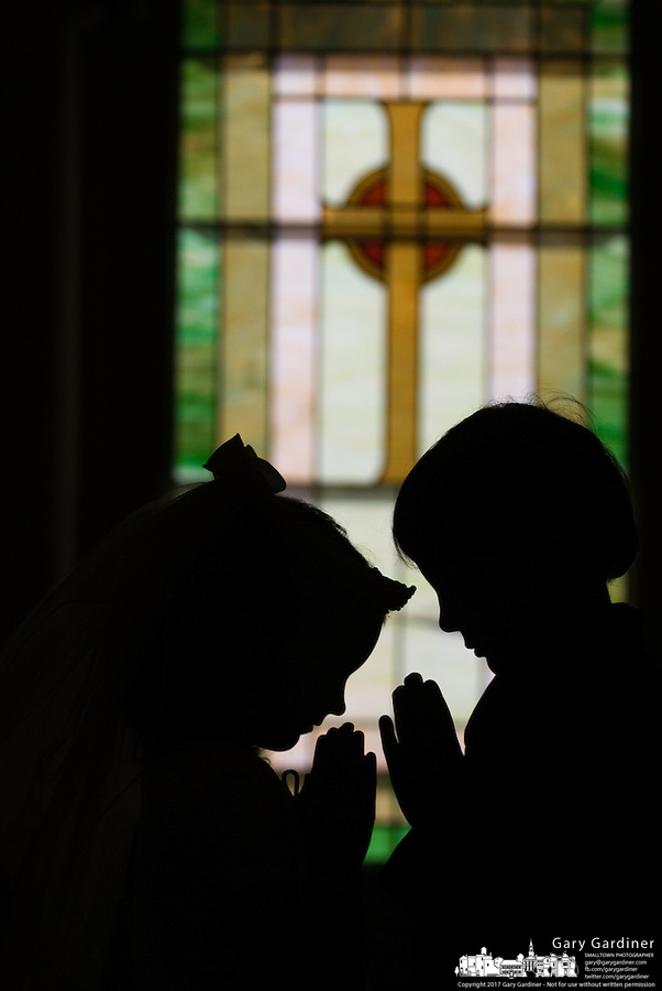 A young girl and boy stand with hands raised in prayer in front of a stained glass window after their first communion sacrament at a Catholic church in Johnstown, OH.<br />