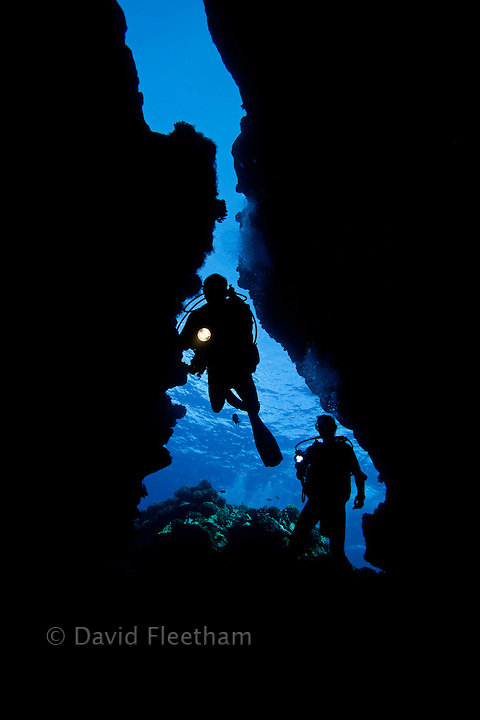 Divers (MR) pictured entering Second Cathedral through the upper crack in the ceiling, off the Island of Lanai, Hawaii.
