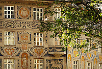 Richly decorated facade at Munich's Rindermarkt; tree leaves. Munich Bavaria Germany.