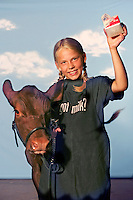 "(7 FairKids Joy Falkenberg 08.03.06)  Cheyenne Cartee (cq) 9 poses at The Ohio State Fair.  She is from New Holland. She had just shown and won some awards with her dairy heffer, Billie Jo (cq).  The ""Got Milk"" apron was not hers.  Photo to go with NOW! package on kids at the Fair.  (Columbus Dispatch Photo by Barth Falkenberg)"