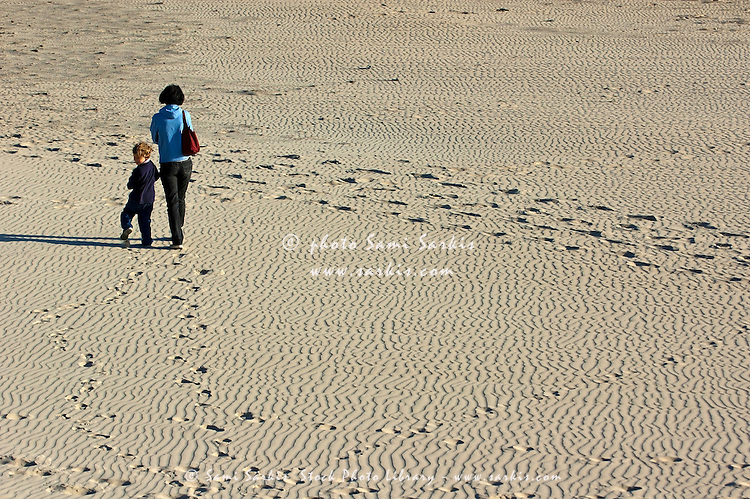 Mother and daughter walking on the beach at Tarifa, Andalusia, Spain.