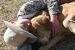 A young red head freckled country boy laying down on the ground resting with his golden retriever dog hug affection love