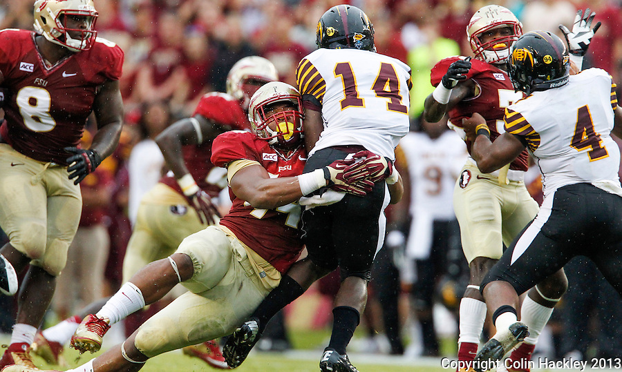 TALLAHASSEE, FLA 9/21/13-FSU-BCC092113CH-Florida State's Demarcus Walker wraps up Bethune-Cookman's Quentin Williams  during first half action Saturday at Doak Campbell Stadium in Tallahassee. <br /> COLIN HACKLEY PHOTO