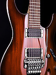 Closeup of brown wood electric guitar Ibanez S-series S420, tremolo and pickups on black background