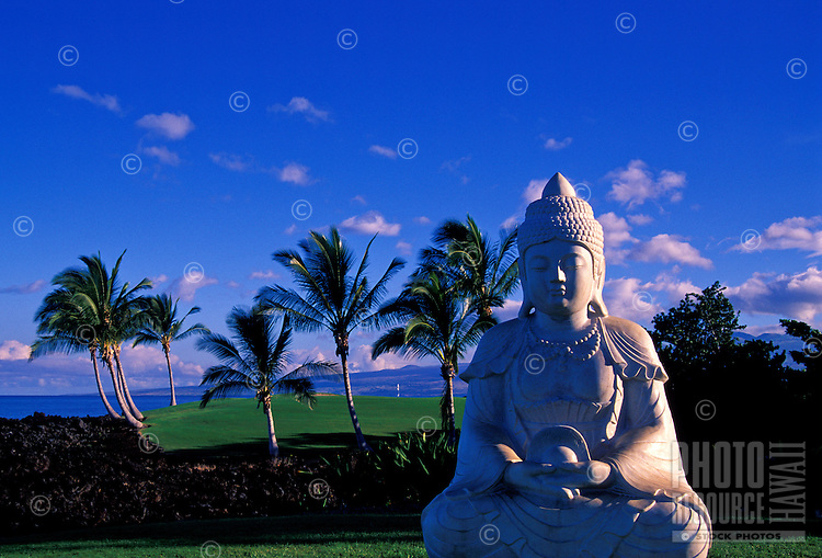 A Buddhist statue in front of a golf course at Hilton Waikoloa Village