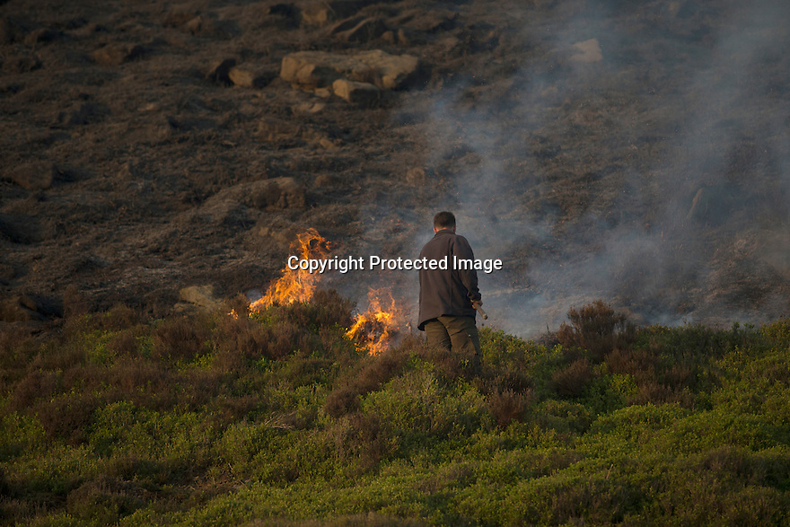 10/05/16 <br /> <br /> After eight hours of tackling a fire high up in a remote part of the Peak District between Sheffield and Manchester, game-keeper, Kieron Logan , continues to beat fresh flames that have burnt some 200 acres of precious heather moorland that was destroyed today after a BBQ started a fire in the valley below.<br /> <br /> Full story:   http://www.fstoppress.com/articles/peak-district-fire/<br /> <br /> .A small group of gamekeepers spent the night fighting a major blaze blaze covering two hundred acres of heather moorland close to the Derwent and Ladybower reservoirs in the Derbyshire Peak District.<br /> <br /> The fire, which broke out at around 1pm on Monday, is believed to have been started by a disposable barbecue, according to a spokesman for the reservoir, which quickly escalated into a major fire threatening the natural habitat of many wild animals and birds including red grouse, plovers, meadow pipits and hen harriers.<br /> <br /> Ten fire crews were called to tackle the flames, and remained on scene until dusk fell, leaving the job of managing the fire overnight to the gamekeepers on scene.<br /> <br /> Kieran Logan was one of the gamekeepers left battling the flames and he said moorland management policies implemented some 10 years ago by the landowners, The National Trust were also partly to blame.<br /> <br /> All Rights Reserved: F Stop Press Ltd. +44(0)1335 418365   +44 (0)7765 242650 www.fstoppress.com