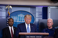 United States President Donald J. Trump, center, makes remarks on the Coronavirus crisis in the Brady Press Briefing Room of the White House in Washington, DC on Saturday, March 21, 2020.  Listening at left is US Secretary of Housing and Urban Development (HUD) Ben Carson and at right is Admiral Brett Giroir, US Assistant Secretary for Health.<br /> Credit: Stefani Reynolds / Pool via CNP/AdMedia
