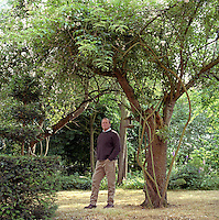 Portrait of garden designer Arne Maynard standing under a tree in his Lincolnshire garden