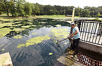 NWA Democrat-Gazette/FLIP PUTTHOFF <br /> WATER WORK<br /> Kimberly Main, property manager at the Illinois River Watershed Partnership, clears algae away from a drain on the partnership's property in downtown Cave Springs. Algae grows on the lake during warm weather, she said.