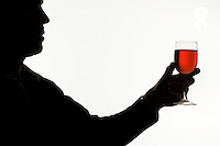Silhouette of man holding glass of red wine (Licence this image exclusively with Getty: http://www.gettyimages.com/detail/sb10068346ay-001 )