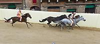 """Siena 02/07/2013: Palio di Siena. Il palio del mese di Luglio è dedicato alla festa di Santa Maria di Provenzano. In ogni Palio prendono parte massimo 10 delle 17 contrade presenti nella città. La scelta viene estratta a sorte. La contrada dell'Oca si è aggiudicato il Palio con il cavallo """"Guess"""" guidato dal fantino Giovanni Atzeni conosciuto come """"Tittia"""".  Nella foto il passaggio dei cavalli nella curva San Martino nel tratto in discesa.  Foto Adamo Di Loreto/BuenaVista*photo"""