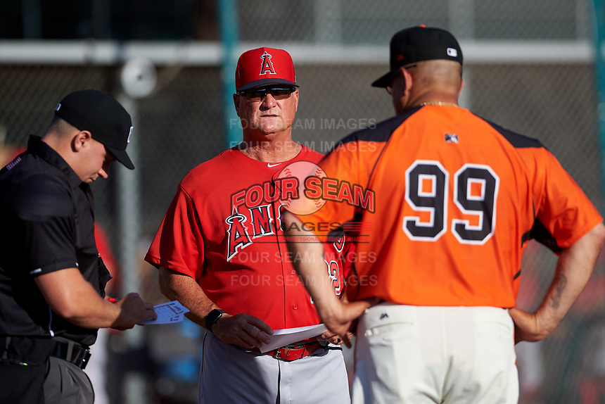AZL Angels manager Dave Stapleton (22) meets with AZL Giants Orange manager Alvaro Espinoza (99) and home plate umpire Luke Morris during the lineup exchange before an Arizona League game at Giants Baseball Complex on June 17, 2019 in Scottsdale, Arizona. AZL Giants Orange defeated AZL Angels 8-4. (Zachary Lucy/Four Seam Images)