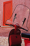 Red scooter against a pink wall, close up