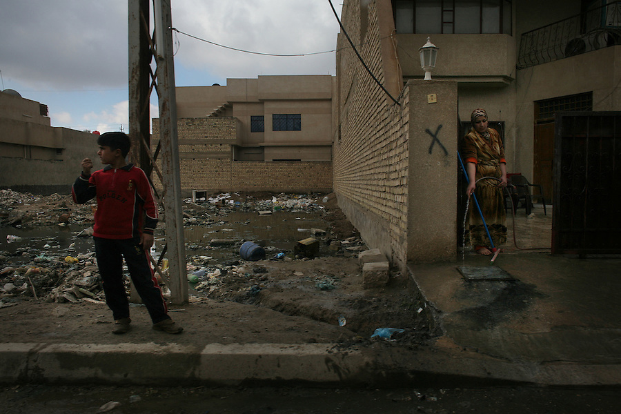 A Sunni woman cleans her driveway hoping to keep the garbage and sewage filling an adjacent lot from making its way into her home in the northwestern Baghdad Ghazaliyah district on Wednesday February 13, 2008. Ghazaliyah is recovering as stability takes hold in the contested district but services such as a functioning sewage system and trash removal are lagging behind security gains. Many Sunnis believe this is the result of intentional neglect by the Shia-led government.