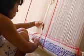 Xingu Indigenous Park, Mato Grosso State, Brazil. Aldeia Samauma (Kaiabi). Kwaryp Kaiabi hand weaving a hammock.
