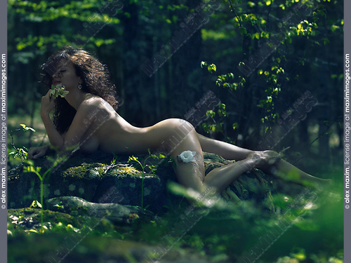 Beautiful sexy nude woman with a flower lying naked on rocks in a deep green forest