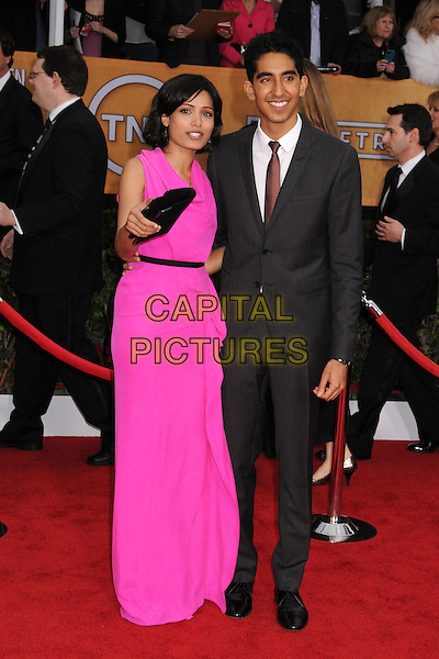 Freida Pinto (wearing Roland Mouret) & Dev Patel .Arrivals at the 19th Annual Screen Actors Guild Awards at the Shrine Auditorium in Los Angeles, California, USA..27th January 2013.SAG SAGs full length pink dress grey hand arm gray suit couple black clutch bag draped.CAP/ADM/BP.©Byron Purvis/AdMedia/Capital Pictures