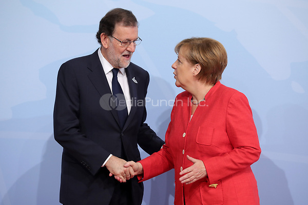 German chancellor Angela Merkel greets the Spanish prime minister Mariano Rajoy at the G20 summit in Hamburg, Germany, 7 July 2017. The heads of the governments of the G20 group of countries are meeting in Hamburg on the 7-8 July 2017. Photo: John Macdougall/POOL AFP/dpa /MediaPunch ***FOR USA ONLY***