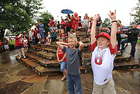 STAFF PHOTO ANDY SHUPE - James Wright, 10, of Anderson, Mo., right, and Justin England, 11, of Neosho, Mo., cheer during an impromptu pep rally while tailgating in The Gardens prior to the start of the University of Arkansas' football game with Nicholls State Saturday, Sept. 6, 2014, at Razorback Stadium in Fayetteville.