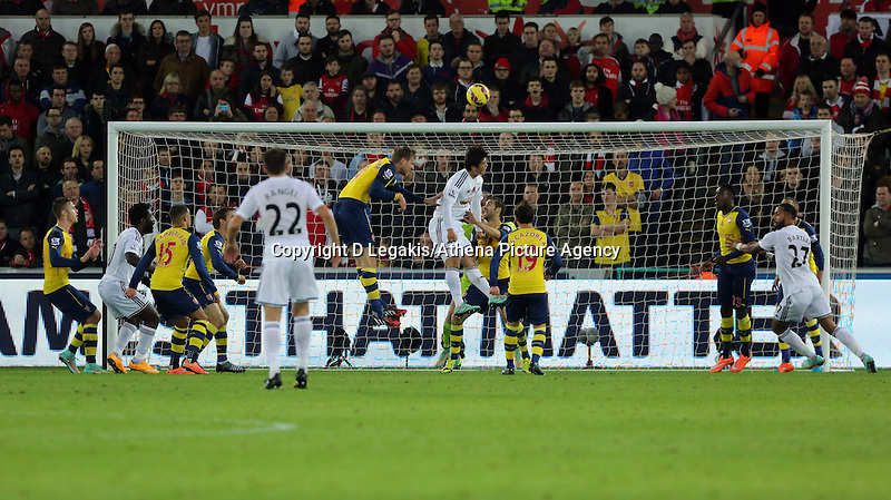 Sunday 09 November 2014 <br /> Ki Sung Yueng of Swansea (C) jumps for a header which goes over the Arsenal bar<br /> Barclays Premier League, Swansea City FC v Arsenal City at the Liberty Stadium, Swansea, Great Britain. EPA/Dimitris Legakis