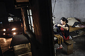 A 50-year-old rural migrant works in a garment sweatshop on the outskirts of the southwestern Chinese megapolis of Chongqing.<br /> <br /> They often work through the nights, earning 1,000 - 6,000 yuan per month depending on work load, a decent income compared with subsistence farming. <br /> <br /> For many, this is a long and arduous step in the transition from farming to urban living. <br /> <br /> China is hoping by relocating farmers into cities they would start to buy food, making a break from the cycle of farmers consuming only what they produce.<br /> <br /> China is pushing ahead with a dramatic, history-making plan to move 100 million rural residents into towns and cities between 2014 and 2020 &mdash; but without a clear idea of how to pay for the gargantuan undertaking or whether the farmers involved want to move.<br /> <br /> Moving farmers to urban areas is touted as a way of changing China&rsquo;s economic structure, with growth based on domestic demand for products instead of exporting them. In theory, new urbanites mean vast new opportunities for construction firms, public transportation, utilities and appliance makers.