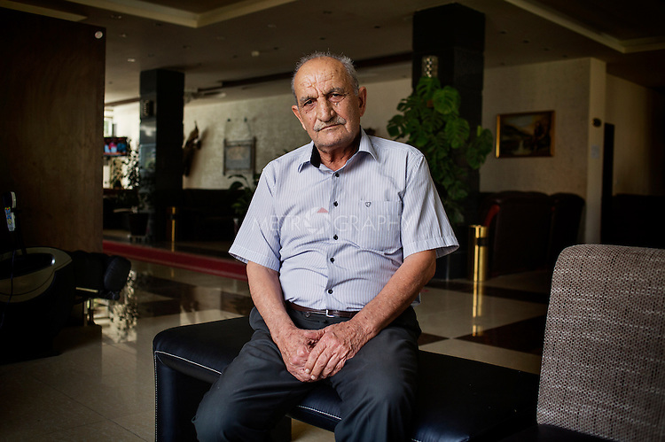 "29/08/15. Shaqlawa, Iraq. -- Nouri, a 70 y.o. retired army officer, now lives at the four star hotel Basma Alsafeer, in Shaqlawa city centre. At the hotel he shares two rooms with his sons' families: one suit for 1million IQD and a room for 700.000 IQD. His sons are all goldsmiths, but they could not find a job suitable for them, and have therefore been without a job for the past 18 months. <br /> <br /> ""Here we don't miss anything, but I feel like a tourist: I hope to go back home soon, I wouldn't have left if my family did not beg me to""."