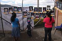 """MEDELLÍN - COLOMBIA, 07-06-2014. Personas ven las imágenes con los nombres de las personas desaparecidas en """"La Escombrera"""", en la Comuna 13 de Medellín, durante una vigilia contra las desapariciones forzadas. En 2002, Medellín fue sacudido por la violencia después de la decisión del Gobierno de recuperar un sector de la ciudad disputada por los paramilitares de derecha y las milicias de izquierda. Según los familiares de las víctimas, en la operación ordenada el 16 de octubre de 2002 por el presidente Álvaro Uribe, decenas de personas murieron, más de 100 personas resultaron heridas, 98 personas desaparecieron y más de 200 familias fueron desplazadas./ People watch the pictures with the names of missing persons in """"La Escombrera"""" in Comuna 13 in Medellín, during a vigil against forced disappearances. In 2002, Medellín was rocked by violence following the government's decision to recover a part of the city disputed by right-wing paramilitaries and leftist militias. According to relatives of the victims, the orderly operation on October 16, 2002 by President Alvaro Uribe, dozens of people were killed, over 100 people were injured, 98 people missing and more than 200 families were displaced. Photo: VizzorImage/Luis Rios/STR"""