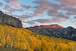 Uncompahgre National Forest, Colorado:<br /> Cliffs of the Cimarron stand above fall colored hillsides in evening, sunset, light, San Juan Mountains