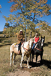 Family group outdoors on a crisp and cool fall morning riding horses on a wrangler-led ride, amid aspen groves high in Rocky Mountain National Park, near Estes Park, Colorado, USA