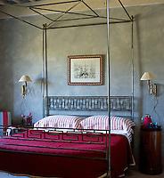 The polished metal four poster bed has a geometric design at its head and foot