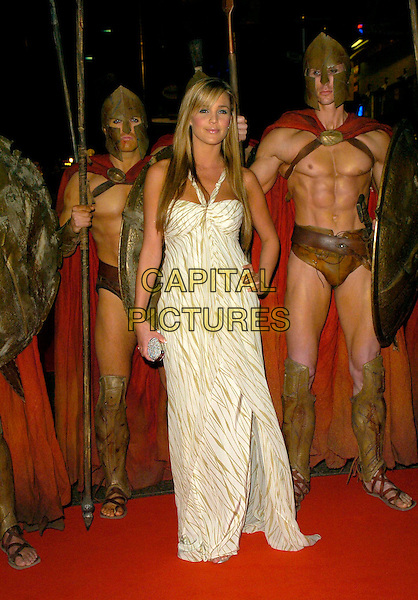 "DANIELLE LLOYD.UK Premiere of ""300"" at Vue West End, Leicester Square, London, UK..full length white beige green pattern dress halterneck silver clutch purse warriors costume dress up armour shields armor hand on hip .CAP/CAN.©Can Nguyen/Capital Pictures"