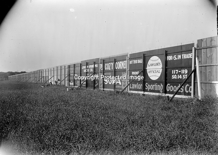 PAINTING THE OUTFIELD FENCE AT LANDIS FIELD, C. 1922. Even Tom Sawyer might not have persuaded anyone to help paint this fence. The businesses advertised on the fence--two sporting goods stores and Cozy Corner soda shop--were founded or relocated to the listed addresses in the early 1920s. Buck Beltzer built Landis Field in 1922 at Second and P Streets, west across the viaduct from downtown Lincoln. It was home to a charter franchise of the Class D Nebraska State League, the Lincoln Links, which returned organized baseball to Lincoln after a five-year hiatus. Beltzer named his field for Kenesaw Mountain Landis, the first commissioner of Major League Baseball. It was home to Nebraska State League and Western League teams until 1939.<br /> <br /> Photographs taken on black and white glass negatives by African American photographer(s) John Johnson and Earl McWilliams from 1910 to 1925 in Lincoln, Nebraska. Douglas Keister has 280 5x7 glass negatives taken by these photographers. Larger scans available on request.