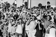 Cape Kennedy, FL - July 16, 1969<br /> An excited crowd gazes up to the sky as Apollo XI hurtles towards the moon.  On the morning of July 16, 1969 astronauts Neil Armstrong and Buzz Aldrin piloted the Apollo XI into space to achieve probably the most historic moment in Space exploration history. Four days later, after entering the lunar orbit, the two touched down in the &lsquo;Sea of Tranquility&rsquo; and Armstrong famously uttered the first words ever spoken by a human on the moon, &lsquo;One small step for man, one giant leap for mankind&rsquo; as he stepped on the moon&rsquo;s surface. <br /> Cape Kennedy, Floride. 16 juillet 1969.<br /> Il est 9h32 du matin la fus&eacute;e qui va porter la capsule Apollo XI sur la lune vient de partir. Les gens la regardent s&rsquo;&eacute;lever, enthousiastes, ils hurlent de joie ! Quatre jours plus tard le 20 juillet Armstrong prononcera cette phrase rest&eacute;e dans les m&eacute;moires&hellip; &ldquo;C&rsquo;est un petit pas pour l&rsquo;homme mais un pas de g&eacute;ant pour l&rsquo;humanit&eacute;&ldquo;.
